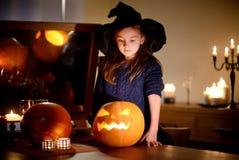 Urocza mała dziewczynka jest ubranym Halloweenowego kostium ma zabawę z rzeźbiącą banią Obrazy Stock