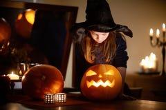 Urocza mała dziewczynka jest ubranym Halloweenowego kostium ma zabawę z rzeźbiącą banią Zdjęcia Stock