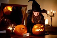 Urocza mała dziewczynka jest ubranym Halloweenowego kostium ma zabawę z rzeźbiącą banią Fotografia Stock