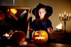 Urocza mała dziewczynka jest ubranym Halloweenowego kostium ma zabawę z rzeźbiącą banią Obraz Stock