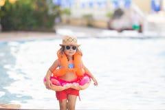 Urocza mała dziewczynka jest ubranym okulary przeciwsłonecznych, nadmuchiwani rękawy unosi się i nadmuchiwany pączka pławika pier zdjęcie royalty free