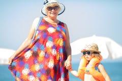 Urocza mała dziewczynka jest ubranym okulary przeciwsłonecznych, nadmuchiwani rękawy unosi się przy plażą z i nadmuchiwana pączka obraz royalty free