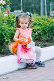 Urocza mała dziewczynka jest ubranym różową suknię po sprzedaży kolorowych torba na zakupy z kędzierzawym włosy Zdjęcia Royalty Free