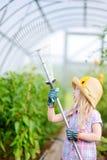 Urocza mała dziewczynka jest ubranym słomianego kapelusz i children ogrodowe rękawiczki bawić się z jej zabawkarskimi ogrodowymi  Zdjęcia Stock