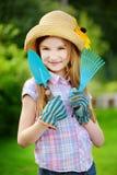 Urocza mała dziewczynka jest ubranym słomianego kapelusz i children ogrodowe rękawiczki trzyma ogrodowych narzędzia Obraz Stock