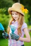 Urocza mała dziewczynka jest ubranym słomianego kapelusz i children ogrodowe rękawiczki trzyma ogrodowych narzędzia Obrazy Stock
