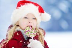 Urocza mała dziewczynka jest ubranym Santa kapelusz ma ogromnego pasiastego Bożenarodzeniowego lizaka na pięknym zima dniu Obraz Royalty Free