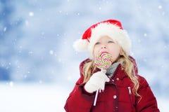 Urocza mała dziewczynka jest ubranym Santa kapelusz ma ogromnego pasiastego Bożenarodzeniowego lizaka na pięknym zima dniu Obrazy Stock
