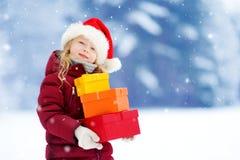 Urocza mała dziewczynka jest ubranym Santa kapelusz trzyma stos Bożenarodzeniowi prezenty na pięknym zima dniu Zdjęcia Stock
