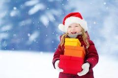 Urocza mała dziewczynka jest ubranym Santa kapelusz trzyma stos Bożenarodzeniowi prezenty na pięknym zima dniu Fotografia Stock