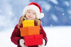 Urocza mała dziewczynka jest ubranym Santa kapelusz trzyma stos Bożenarodzeniowi prezenty na pięknym zima dniu Zdjęcia Royalty Free
