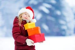 Urocza mała dziewczynka jest ubranym Santa kapelusz trzyma stos Bożenarodzeniowi prezenty na pięknym zima dniu Obrazy Stock