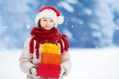 Urocza mała dziewczynka jest ubranym Santa kapelusz trzyma stos Bożenarodzeniowi prezenty na pięknym zima dniu Obrazy Royalty Free