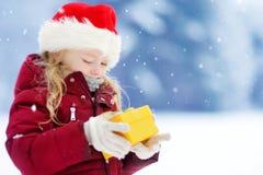 Urocza mała dziewczynka jest ubranym Santa kapeluszowego mienia Bożenarodzeniowego prezent na pięknym zima dniu Obrazy Stock