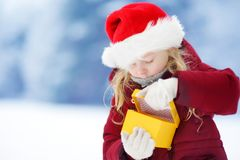 Urocza mała dziewczynka jest ubranym Santa kapeluszowego mienia Bożenarodzeniowego prezent na pięknym zima dniu Obrazy Royalty Free