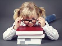 Urocza mała dziewczynka jest ubranym szkła i trzyma książki zdjęcie royalty free