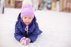 Urocza mała dziewczynka kłaść na łyżwiarskim lodowisku póżniej obrazy stock