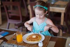Urocza mała dziewczynka ma śniadanie przy kurortem Obraz Stock