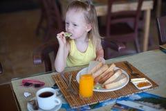 Urocza mała dziewczynka ma śniadanie przy kurortem Obrazy Stock