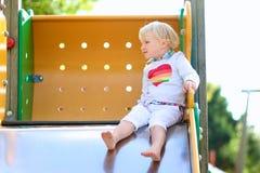Urocza mała dziewczynka ma zabawę przy boiskiem Fotografia Stock