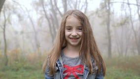 Urocza mała dziewczynka ono uśmiecha się w kamerę zbiory