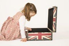 Urocza mała dziewczynka patrzeje inside rettro walizkę Obrazy Royalty Free