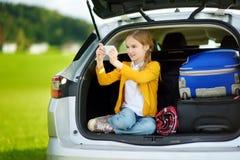 Urocza mała dziewczynka przygotowywająca iść na wakacjach z jej rodzicami Dzieciak bierze obrazkom z ona telefon w samochodzie Obraz Stock