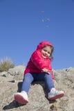 Urocza mała dziewczynka rzuca małych kamienie kamera obraz royalty free