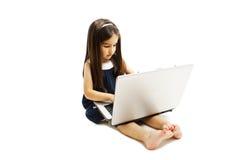 Urocza mała dziewczynka siedzi na podłoga z jej laptopem Fotografia Royalty Free