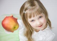 Urocza mała dziewczynka trzyma dojrzałego jabłka Obraz Stock