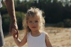 Urocza mała dziewczynka trzyma jej ojciec rękę w biel sukni Portret piękna caucasian dziewczyna z długim białym włosy zdjęcie stock