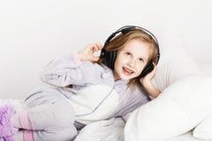 Urocza mała dziewczynka w hełmofonach cieszy się z muzyką zdjęcie royalty free