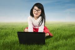 Urocza mała dziewczynka z laptopem przy łąką Obraz Royalty Free