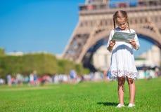 Urocza mała dziewczynka z mapą Paryski tło Obraz Royalty Free