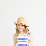 Urocza mała dziewczynka z słomianym kapeluszem przeciw białemu tłu Fotografia Royalty Free