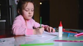 Urocza mała Kaukaska dziewczyna w różowym puloweru rysunku kształtuje z ołówkiem na prześcieradle papier, opowiada someone zbiory wideo