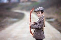 Urocza mała preschool chłopiec, krótkopęd z łękiem i strzała przy targe, Zdjęcia Royalty Free