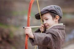 Urocza mała preschool chłopiec, krótkopęd z łękiem i strzała przy targe, Obraz Stock