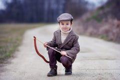Urocza mała preschool chłopiec, krótkopęd z łękiem i strzała przy targe, Obrazy Royalty Free