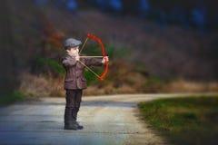 Urocza mała preschool chłopiec, krótkopęd z łękiem i strzała przy targe, Obrazy Stock