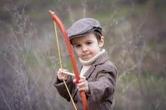 Urocza mała preschool chłopiec, krótkopęd z łękiem i strzała przy targe, Zdjęcie Stock