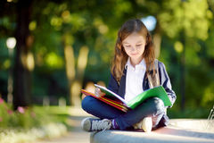 Urocza mała uczennica studiuje outdoors na jaskrawym jesień dniu Młody uczeń robi jej pracie domowej Edukacja dla małych dzieciak Obrazy Stock
