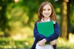 Urocza mała uczennica studiuje outdoors na jaskrawym jesień dniu Młody uczeń robi jej pracie domowej Edukacja dla małych dzieciak Zdjęcia Stock