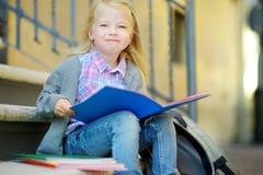 Urocza mała uczennica studiuje outdoors na jaskrawym jesień dniu Młody uczeń robi jej pracie domowej Edukacja dla małych dzieciak Zdjęcia Royalty Free