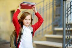 Urocza mała uczennica studiuje outdoors na jaskrawym jesień dniu Młody uczeń robi jej pracie domowej Edukacja dla małych dzieciak Zdjęcie Royalty Free