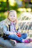 Urocza mała uczennica w miasto parku na jaskrawym jesień dniu Obrazy Stock
