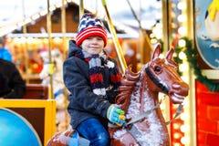 Urocza małe dziecko chłopiec jazda na carousel koniu przy Bożenarodzeniowym funfair lub rynkiem, outdoors obraz stock