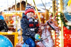 Urocza małe dziecko chłopiec jazda na wesoło iść round carousel koń przy Bożenarodzeniowym funfair lub rynkiem, outdoors szczęśli obrazy stock