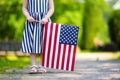 Urocza małej dziewczynki mienia flaga amerykańska outdoors na pięknym letnim dniu Fotografia Stock