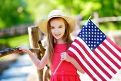 Urocza małej dziewczynki mienia flaga amerykańska outdoors na pięknym letnim dniu Obraz Royalty Free